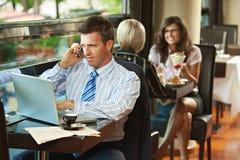 Hombre de negocios usando la computadora portátil en café Foto de archivo libre de regalías