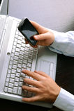 Hombre de negocios usando la computadora portátil y el teléfono móvil Foto de archivo