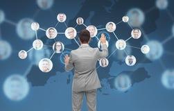 Hombre de negocios usando la pantalla virtual con los contactos Foto de archivo libre de regalías
