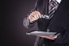 Hombre de negocios usando la tableta con la lupa imagenes de archivo