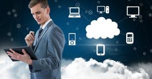 Hombre de negocios usando la tableta digital contra concepto computacional de la nube en cielo Foto de archivo