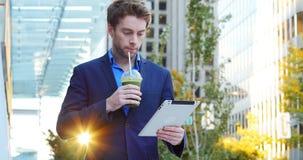 Hombre de negocios usando la tableta digital mientras que comiendo jugo almacen de video