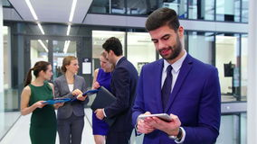 Hombre de negocios usando la tableta digital mientras que empresarios que discuten en fondo metrajes