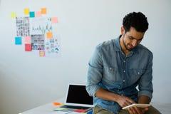Hombre de negocios usando la tableta digital mientras que se sienta en el escritorio Imagen de archivo libre de regalías