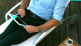 Hombre de negocios usando la tableta en deckchair almacen de metraje de vídeo