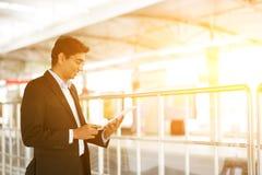 Hombre de negocios usando la tableta en el ferrocarril Imágenes de archivo libres de regalías