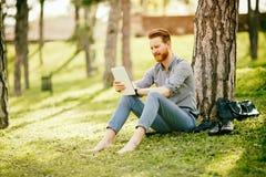 Hombre de negocios usando la tableta en parque Fotografía de archivo