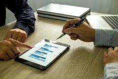 Hombre de negocios usando la tableta a enseñar y el análisis la situación encendido imagen de archivo libre de regalías