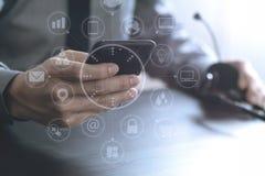 hombre de negocios usando las auriculares de VOIP con el teléfono móvil y COM del concepto Imagenes de archivo