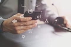 hombre de negocios usando las auriculares de VOIP con el teléfono móvil y COM del concepto Imagen de archivo libre de regalías
