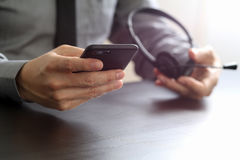 hombre de negocios usando las auriculares de VOIP con el teléfono móvil y COM del concepto Imágenes de archivo libres de regalías