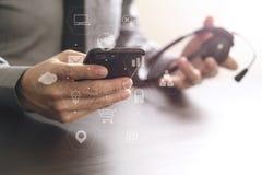 hombre de negocios usando las auriculares de VOIP con el teléfono móvil y COM del concepto Fotos de archivo libres de regalías