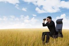 Hombre de negocios usando los prismáticos en campo de trigo Imagen de archivo libre de regalías