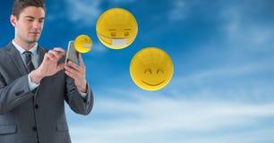 Hombre de negocios usando los teléfonos elegantes mientras que emojis que vuelan contra el cielo stock de ilustración