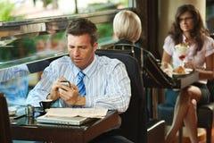 Hombre de negocios usando móvil en café Imágenes de archivo libres de regalías