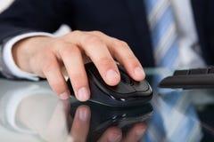 Hombre de negocios usando ratón del ordenador en el escritorio Fotos de archivo libres de regalías