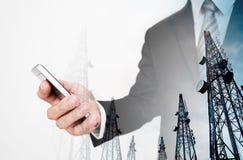 Hombre de negocios usando smartphone, con la torre de la telecomunicación de la exposición doble imagen de archivo