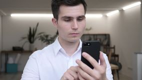 Hombre de negocios usando smartphone en oficina metrajes