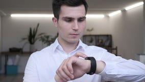 Hombre de negocios usando smartwatch en oficina metrajes