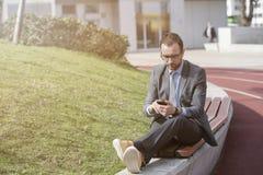 Hombre de negocios usando su teléfono elegante mientras que descansa sobre el banco Fotografía de archivo libre de regalías