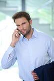 Hombre de negocios usando su teléfono en la oficina - hombre de negocios acertado - camisa azul Foto de archivo libre de regalías