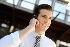 Hombre de negocios usando un teléfono elegante en un edificio de oficinas Fotografía de archivo libre de regalías