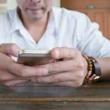Hombre de negocios usando un teléfono móvil con el mensaje que manda un SMS Imagenes de archivo