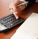 Hombre de negocios usando una calculadora Imagen de archivo