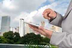 Hombre de negocios usando una PC de la tableta con paisaje urbano Imágenes de archivo libres de regalías