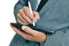 Hombre de negocios usando una pluma de la aguja en su tableta fotografía de archivo libre de regalías