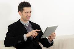 Hombre de negocios usando una tablilla de la pantalla táctil Imágenes de archivo libres de regalías