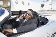 Hombre de negocios Using Cell Phone en convertible Foto de archivo libre de regalías