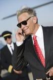 Hombre de negocios Using Cell Phone en el campo de aviación Foto de archivo libre de regalías