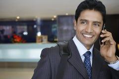 Hombre de negocios Using Cell Phone en pasillo del hotel Foto de archivo