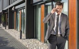Hombre de negocios Using Cell Phone fuera de la oficina Fotografía de archivo