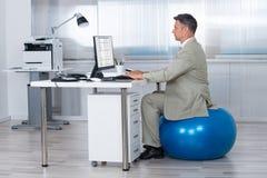 Hombre de negocios Using Computer While que se sienta en bola del ejercicio Imagen de archivo