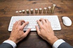 Hombre de negocios Using Keyboard In Front Of Stacked Coins Imágenes de archivo libres de regalías