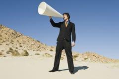 Hombre de negocios Using Megaphone en desierto foto de archivo libre de regalías