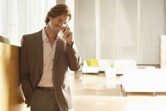 Hombre de negocios Using Mobile Phone en oficina Imágenes de archivo libres de regalías