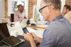 Hombre de negocios Using Mobile Phone en oficina creativa Foto de archivo libre de regalías