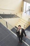 Hombre de negocios Using Mobile Phone mientras que hace una pausa la verja de cristal imagen de archivo