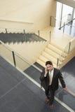 Hombre de negocios Using Mobile Phone mientras que se inclina en la verja de cristal imagen de archivo
