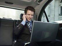 Hombre de negocios Using Mobile Phone y ordenador portátil en coche Foto de archivo