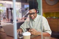 Hombre de negocios Using Phone Working en el ordenador portátil en cafetería Fotos de archivo libres de regalías