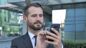 Hombre de negocios Using Smartphone de la barba para hojear en línea almacen de video