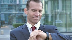 Hombre de negocios Using Smartwatch para hojear almacen de metraje de vídeo