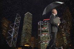 Hombre de negocios Walking Against Cityscape en un día lluvioso en la noche imagenes de archivo
