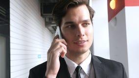 Hombre de negocios Walking y el hablar en Smartphone fotografía de archivo libre de regalías