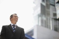 Hombre de negocios Wearing Wireless Headset contra el cielo Imágenes de archivo libres de regalías