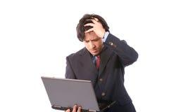 Hombre de negocios woried joven que trabaja con la computadora portátil Imagenes de archivo